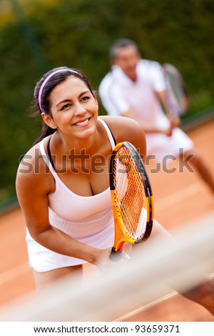 Couple playing doubles at the tennis court - stock photo
