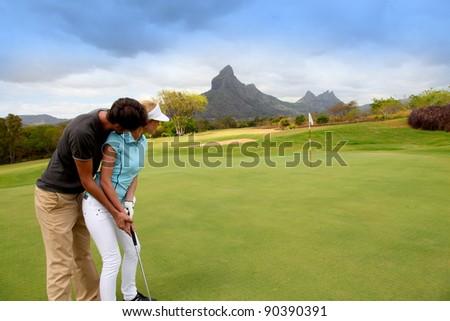Couple playing golf - stock photo