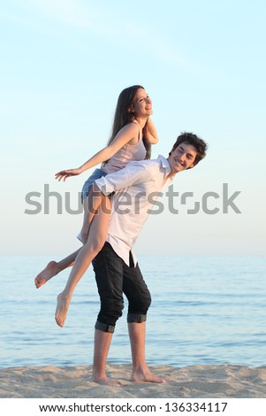 Couple playing piggyback on the beach at sunset with the sea in the background - stock photo
