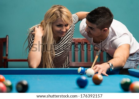 Couple Playing Pool At The Bar - Young Caucasian Man Receiving Advice On Shooting Pool Ball While Playing Billiards - stock photo