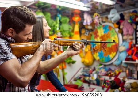 couple playing shooting games while visiting an amusement park, young man holding gun and shooting  - stock photo