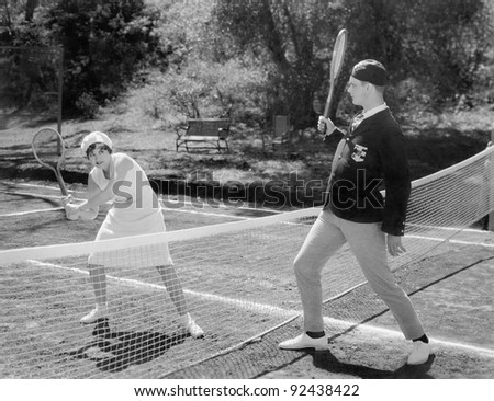 Couple playing tennis together - stock photo