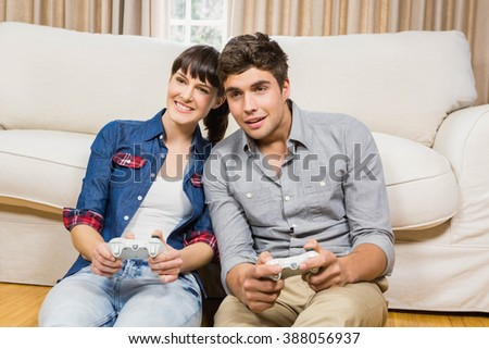 Couple playing video game in their living room - stock photo