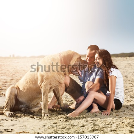 couple playing with dog on the beach. - stock photo