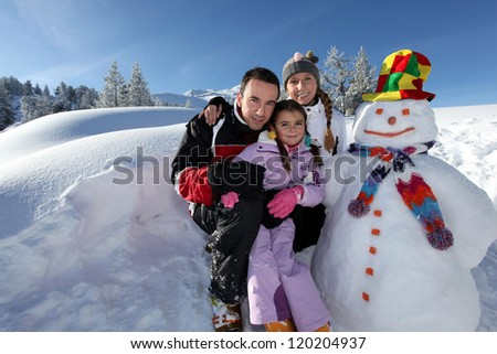 couple posing with child beside snowman at mountain resort - stock photo