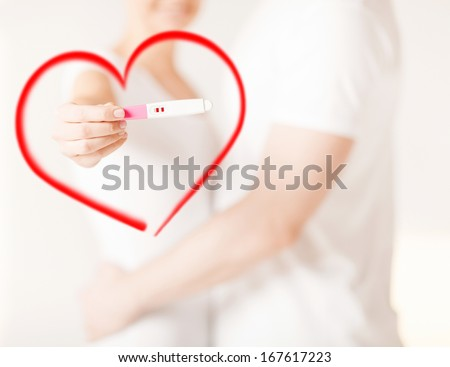 couple, pregnancy and love concept - close up of woman and man hands with pregnancy test - stock photo