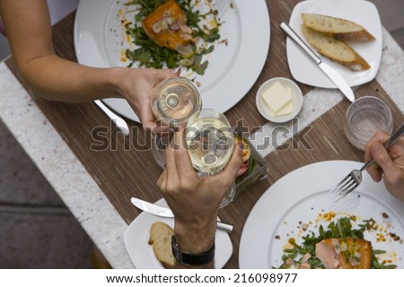 Couple proposing toast with wine glasses at dinner table, elevated view - stock photo