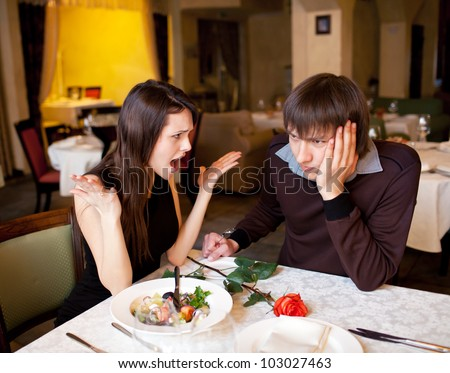 couple quarrels at restaurant and girl screams at the guy - stock photo