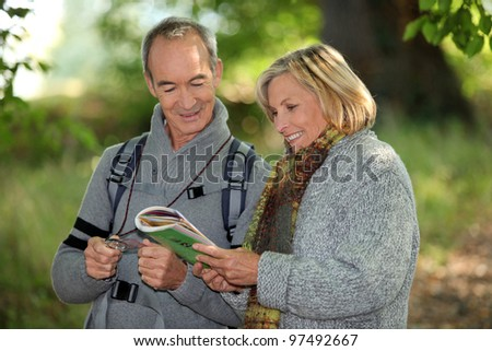 Couple reading a map in a forest - stock photo