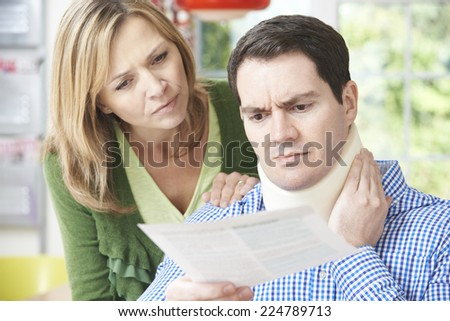 Couple Reading Letter In Respect Of Husband's Neck Injury - stock photo