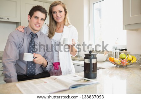 Couple reading newspaper and drinking coffee in kitchen - stock photo