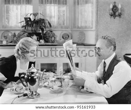 Couple reading newspaper at breakfast table - stock photo