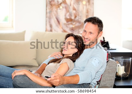 Couple relaxing at home in front of tv - stock photo