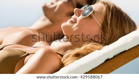 couple relaxing at the deck chairs by the pool in summer - stock photo