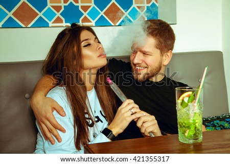 couple relaxing at the shisha bar and laughing. Couple smokes hookah and drinks cocktail - stock photo