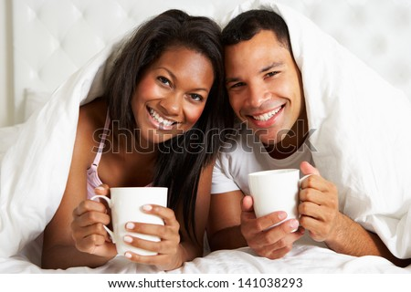 Couple Relaxing In Bed With Hot Drink - stock photo