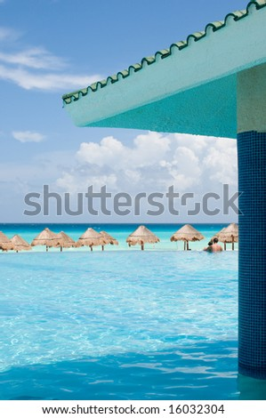Couple relaxing in infinity pool, staring at the ocean, in luxury tropical resort - focus on foreground - stock photo