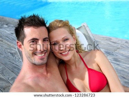 Couple relaxing in long chairs by swimming-pool - stock photo