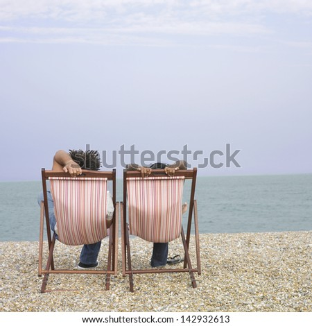 Couple relaxing in lounge chairs at the beach - stock photo