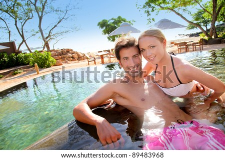Couple relaxing in luxury hotel swimming-pool - stock photo