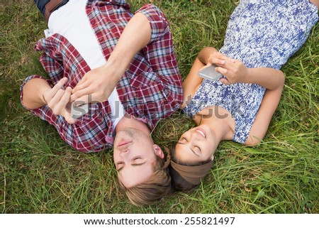 Couple relaxing in the park on their phones on a sunny day - stock photo