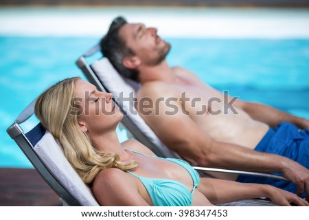 Couple relaxing on a sun lounger near pool - stock photo
