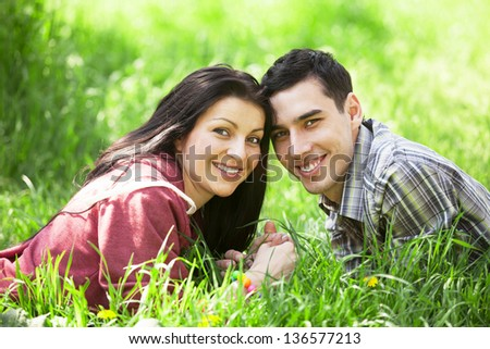 Couple Relaxing on Green Grass.Park. - stock photo