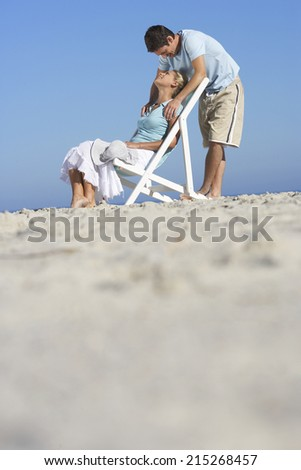 Couple relaxing on sandy beach, man standing behind woman in deckchair, surface level - stock photo