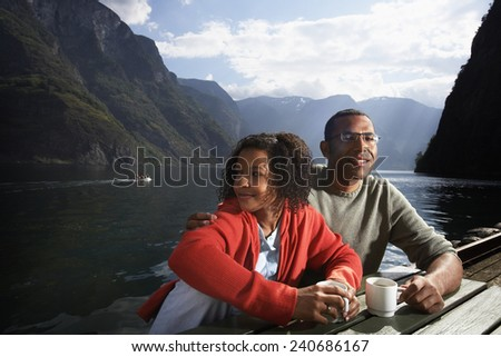 Couple Relaxing on Shore of Fjord - stock photo