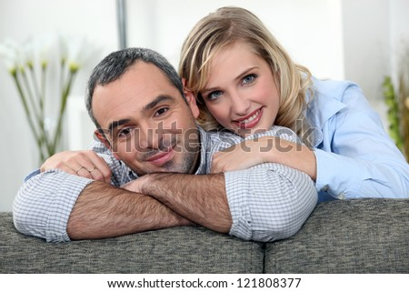 Couple relaxing on sofa - stock photo