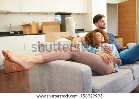 Couple Relaxing On Sofa With Hot Drink In New Home - stock photo