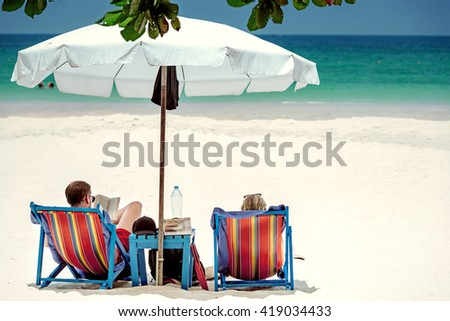 Couple relaxing on tropical beach - stock photo