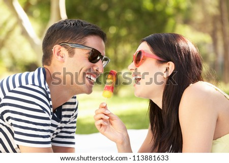 Couple Relaxing Together In Garden Eating Ice Lolly - stock photo