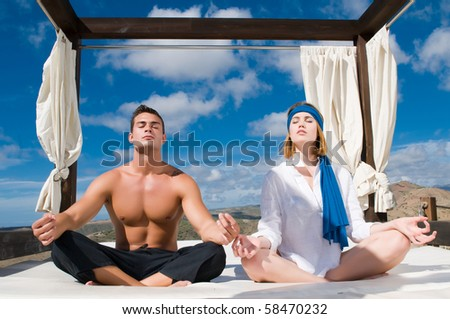 couple relaxing under sky and white clouds - stock photo