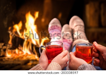 Couple relaxing with mulled wine at romantic fireplace on winter evening - stock photo