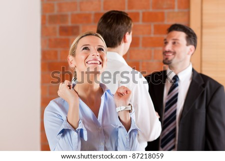 Couple renting apartment from a realtor - a woman is happy about it and stands in the front while in the back the men shaking hands - stock photo
