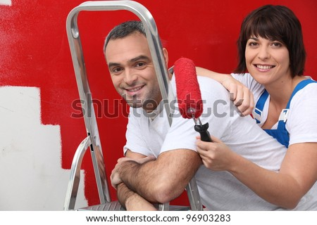 couple repainting their apartment - stock photo