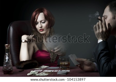Couple - rich woman and man in suit playing poker, drink whiskey and smoke cigar. Retro style - stock photo