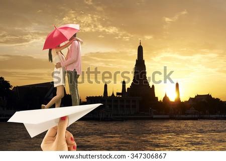 Couple ride paper plane on Wat Arun silhouette on sunset background,Bangkok,Thailand - stock photo