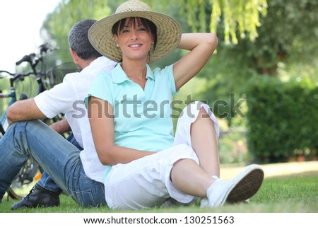 couple riding bikes and relaxing in the park - stock photo