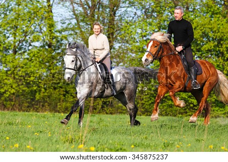 Couple riding horse in summer meadow. - stock photo