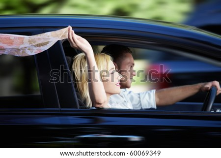 Couple riding in a car at high speed - stock photo