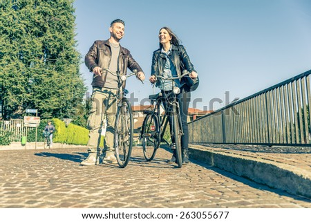 Couple riding on bicycles  and having fun - Tourists driving around the city - Two friends walking with bikes on the streets - stock photo