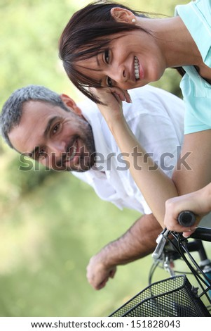 Couple riding their bikes together - stock photo
