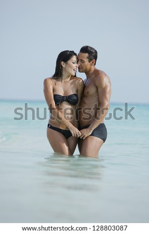 Couple romancing in water on the beach - stock photo