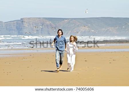 Couple running at the beach enjoying - stock photo