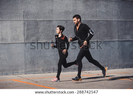 Couple running in an urban environment - stock photo