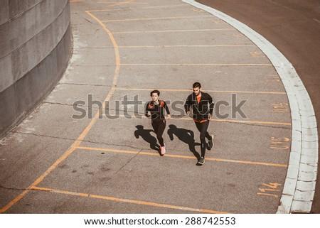 Couple running in an urban environment. Bird`s eye view - stock photo