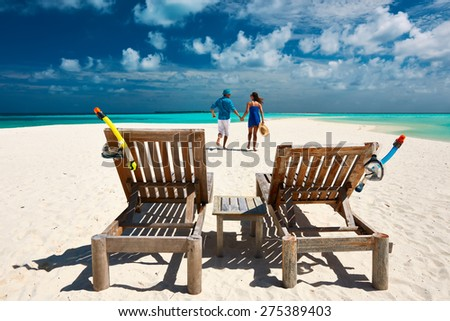 Couple running on a tropical beach at Maldives - stock photo