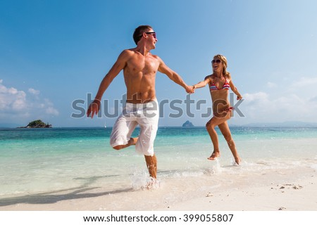 Couple running on the tropical beach - stock photo